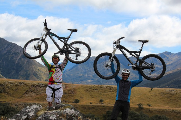 Previous participants in one of The James Mountain Bike events holding their bikes aloft.